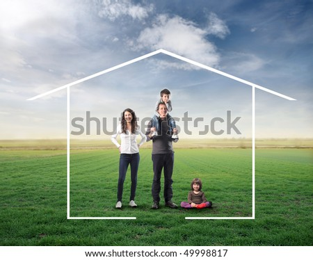 Family surrounded by the form of a house on a green meadow - stock photo