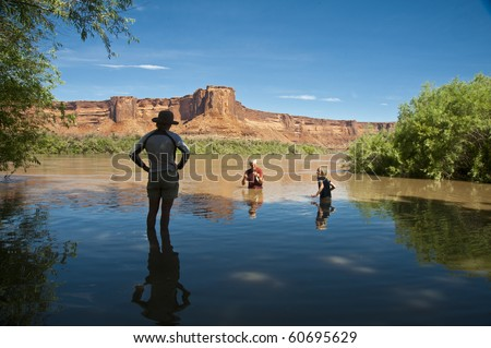 Family swimming in desert river in the canyon country of Utah