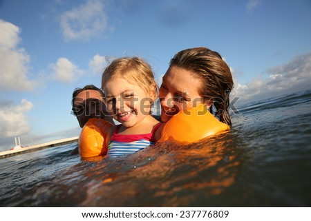Family swimming in sea at sunset - stock photo