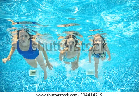 Family swims in pool under water, happy active mother and children have fun underwater, kids sport on family vacation  - stock photo
