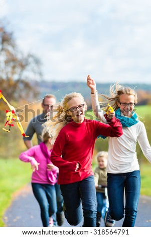 Family take walk in autumn forest flying kite - stock photo