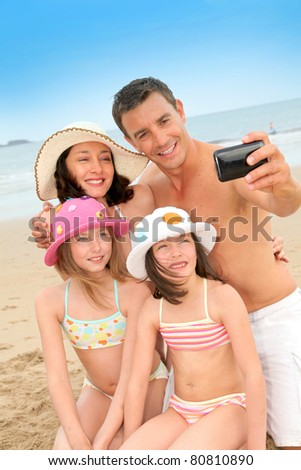 Family taking picture of themselves at the beach - stock photo