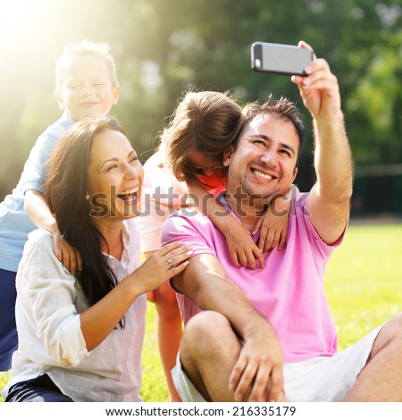 family taking selfies with smartphone in park - stock photo