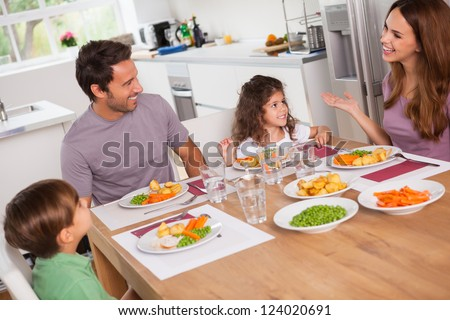 Family talking around the dinner table in kitchen - stock photo