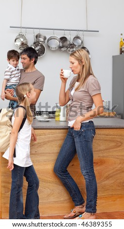 Family talking in the kitchen before going to school during breakfast - stock photo