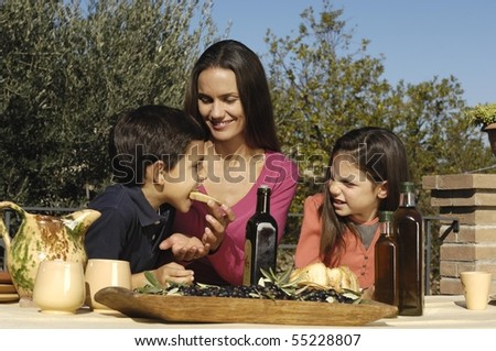 family tasting oil and bread - stock photo