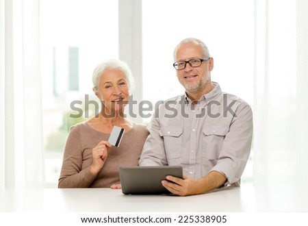 family, technology, age and people concept - happy senior couple with tablet pc computer and credit card at home