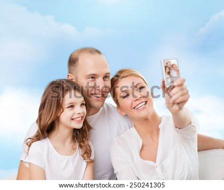 family, technology and people concept - smiling mother, father and little girl making selfie with camera over blue sky background - stock photo