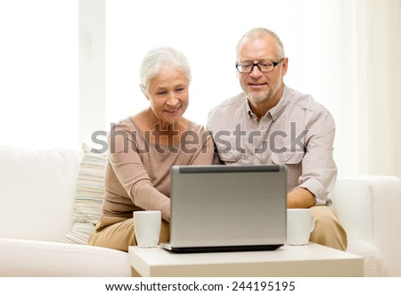 family, technology, drinks, age and people concept - happy senior couple with laptop computer and cups at home - stock photo