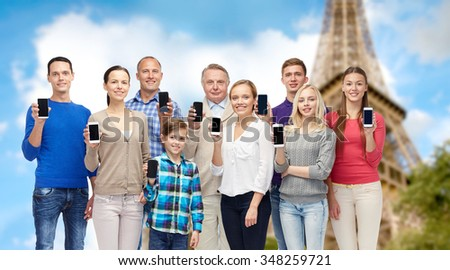 family, technology, travel and tourism concept - group of smiling people  with smartphones over eiffel tower background