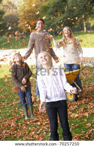 Family throwing autumn leaves into the air in garden - stock photo