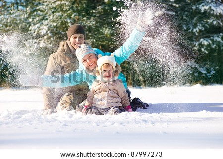 Family throwing snow in park - stock photo