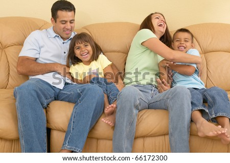 Family tickling each other on the sofa - stock photo