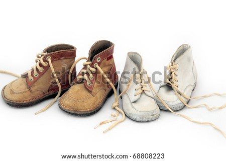 Family ties: two pairs of vintage baby shoes, boy's and girl's, tied together. Shot on white background. - stock photo
