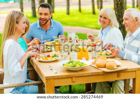 Family time. Happy family of five people communicating and enjoying meal together while sitting at the dining table outdoors  - stock photo