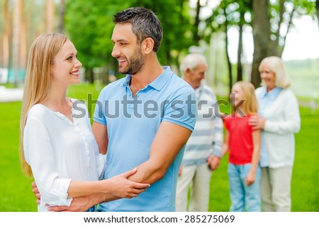 Family time. Happy young couple bonding and looking at each other while grandparents and little girl standing in the background  - stock photo