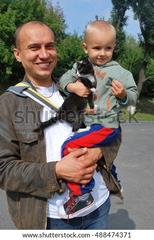 Family time in a park: father is holding his son, while son is holding a black-and-white kitten.