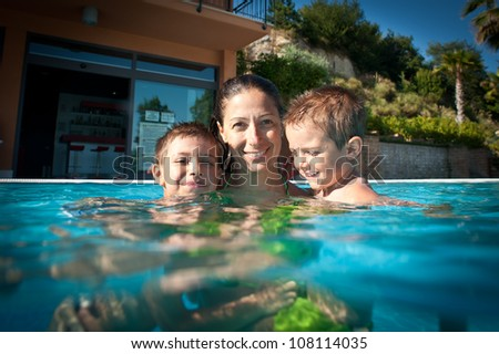 Family time in swimming pool. - stock photo