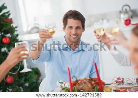 Family toasting at christmas dinner in the dinning room - stock photo