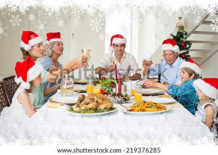 Family toasting wine while having Christmas meal against fir tree forest and snowflakes - stock photo