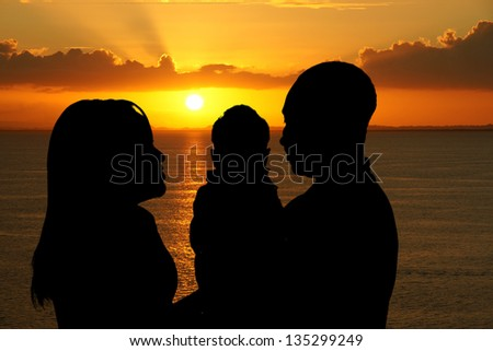 Family together outside at the beach silhouette - stock photo