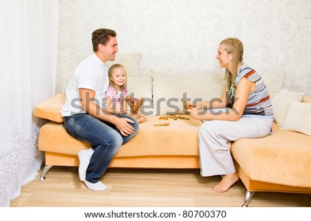 Family together playing dominoes on the couch - stock photo