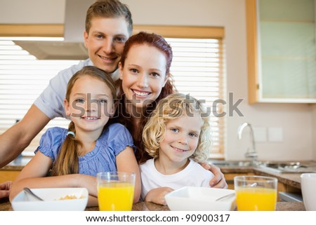 Family together with breakfast behind the kitchen counter - stock photo