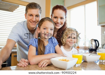 Family together with breakfast in the kitchen - stock photo