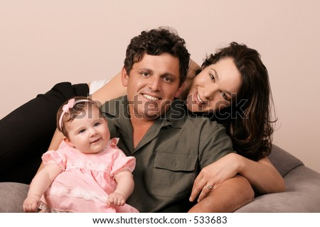Family Togetherness - Mum, Dad and baby girl 5mths. This is also a multicultural family.  Both parents are from different backgrounds / nationalities - stock photo