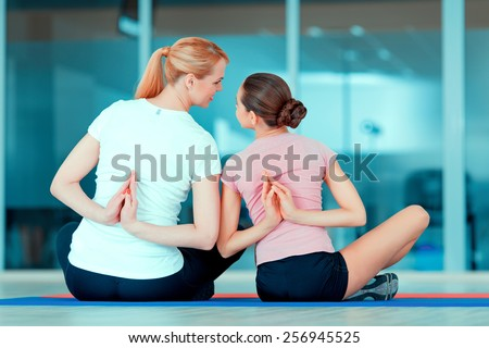 Family training. Rear view image of beautiful teenage girl and her mother in sports clothing training yoga on the mat in sports club - stock photo