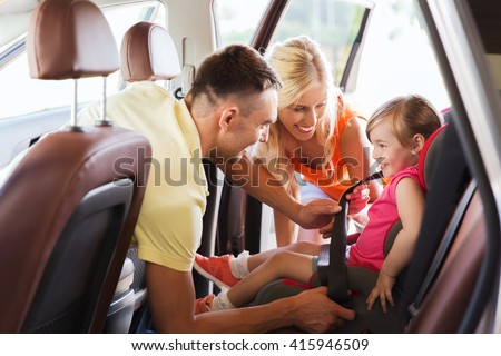 family, transport, road trip and people concept - happy parents fastening child with safety belt in baby car seat - stock photo