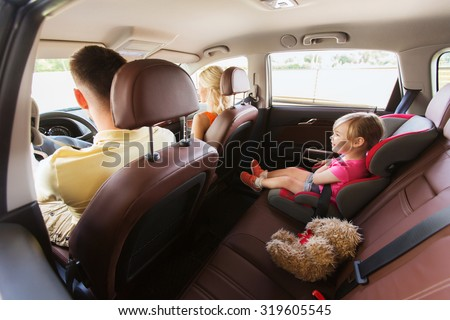 family, transport, safety, road trip and people concept - happy parents with little child driving in car - stock photo