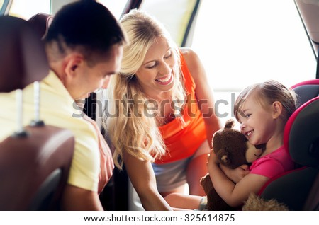 family, transport, safety, road trip and people concept - happy parents with to little girl in baby car seat hugging teddy bear toy - stock photo