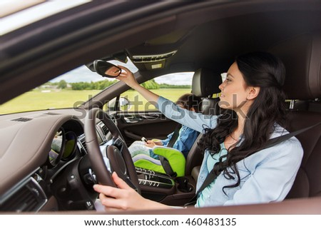 family, transport, safety, road trip and people concept - happy woman with little daughter driving car and looking to rearview mirror