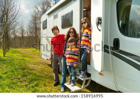 Family travel in motorhome (RV) on vacation, happy parents and kids having fun near camper  - stock photo