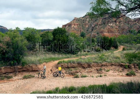 Family traveling on bicycles stopped before the obstacle. Palo Duro Canyon State Park, Texas, US - stock photo
