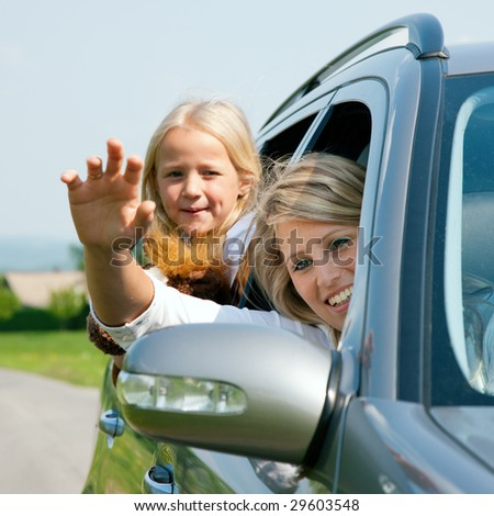 Family travelling by car, mother waving with hands - stock photo