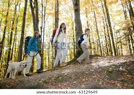 Family trekking with dog - stock photo