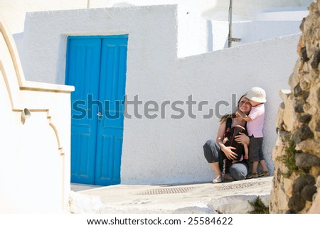 Family trip to Europe. Young mother with two kids exploring Greek town. - stock photo