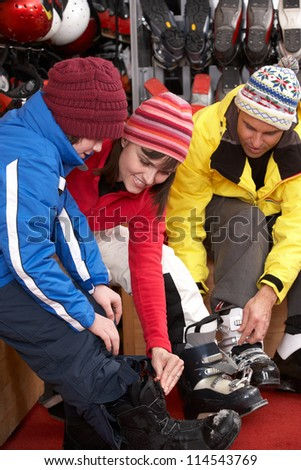 Family Trying On Ski Boots In Hire Shop - stock photo