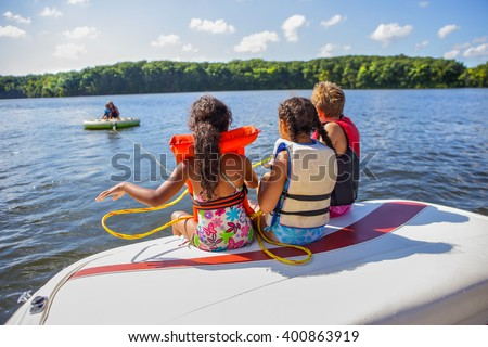 Family tubing from a boat on an inland lake - stock photo