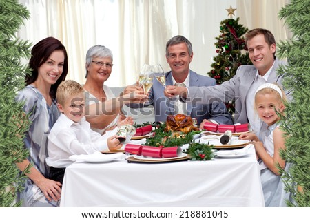 Family tusting in a Christmas dinner against green fir branches