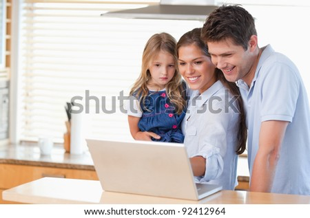 Family using a laptop in a kitchen - stock photo