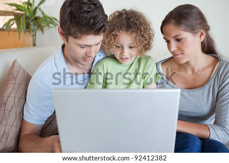 Family using a laptop while sitting on a sofa