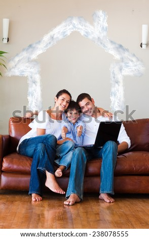 Family using a laptop with thumbs up and copyspace against house outline in clouds - stock photo