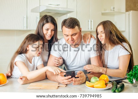family using cell phone while cooking at kitchen