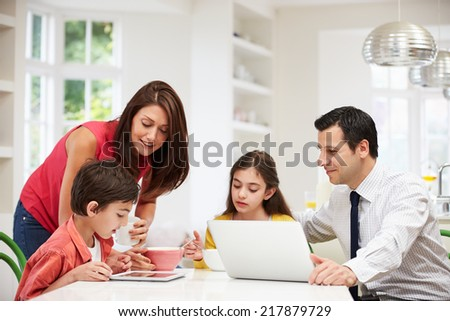 Family Using Digital Devices At Breakfast Table - stock photo