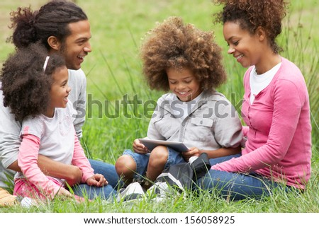 Family Using Digital Tablet Whilst Hiking In Countryside