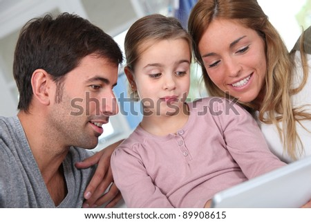 Family using electronic tablet at home - stock photo