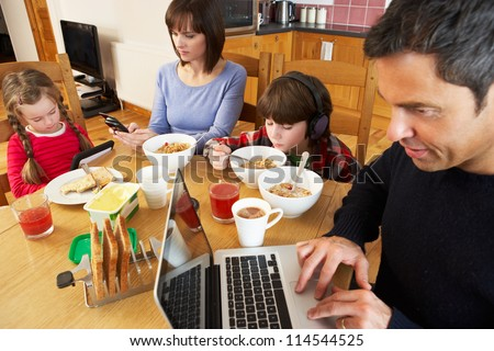 Family Using Gadgets Whilst Eating Breakfast Together In Kitchen - stock photo